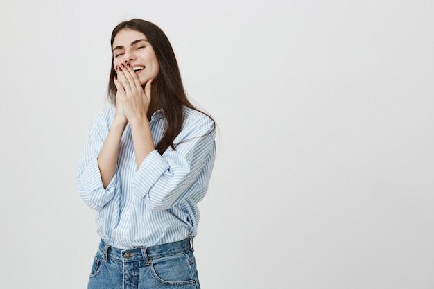 Милая молодая женщина хихикает, прикрывая улыбку руками