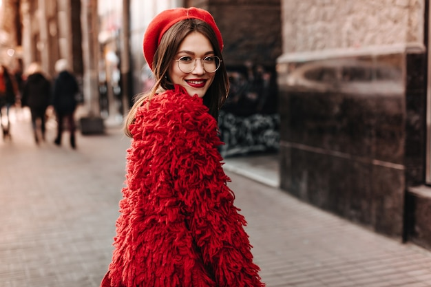 Cute young woman in glasses walks through city. brunette with red lipstick dressed in bright eco-coat and beret posing against background of building.