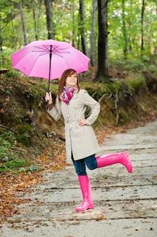 雨が降った後に楽しんでいるかわいい若い女性