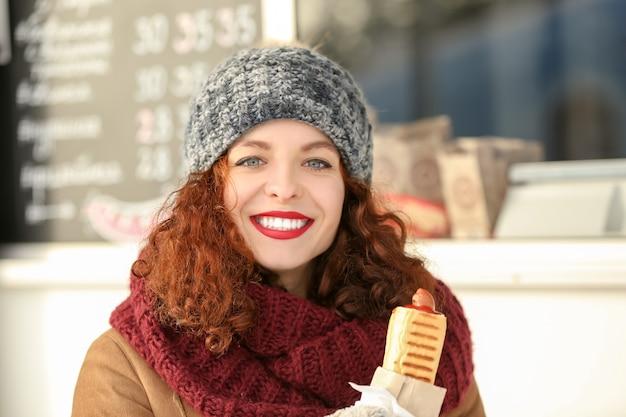 Cute young woman having lunch break on winter market