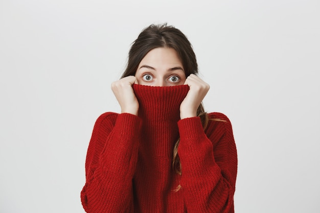 Cute young woman hiding head in sweater collar, peeking camera