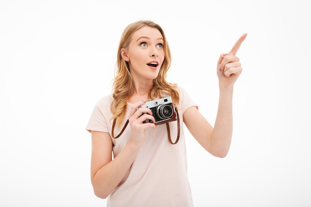 Cute young woman holding camera pointing.