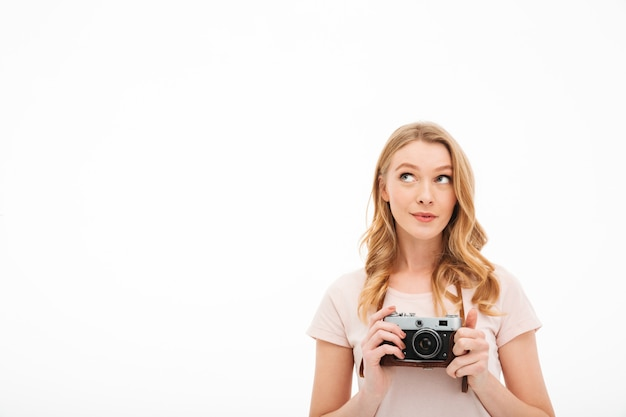 Cute young woman holding camera.