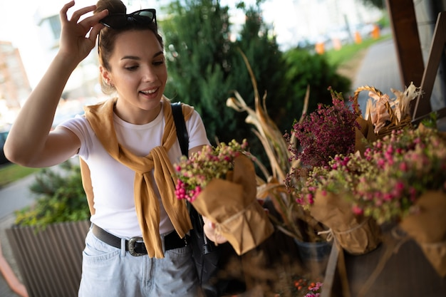 ストリートガーデンショップで彼女のお気に入りの花を保持しているかわいい若い女性