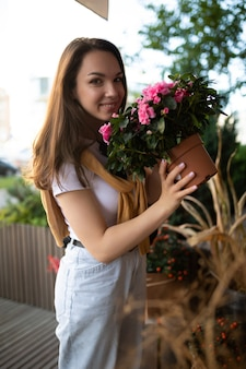 Cute young woman holding her favorite flowers in a street garden shop