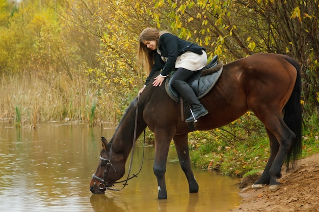 Cute young woman on horse in autumn forest by lake. horse drinks water in pond, female strokes her mane. rider in autumn park