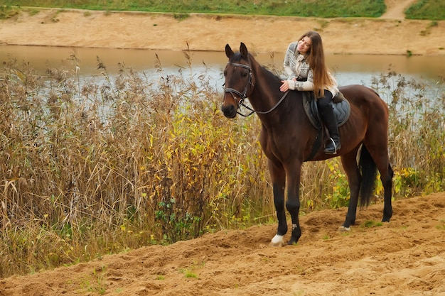 Cute young woman on horseback in autumn forest by lake. rider female drives her horse in park in inclement cloudy weather with rain