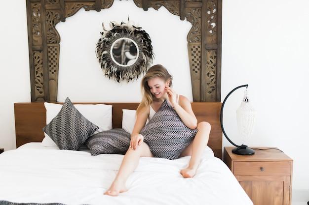 Милая молодая женщина обнимает подушку, сидя в спальне