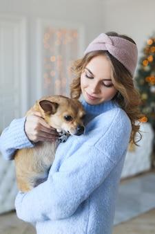 ペットの犬が木のそばで抱き合ったりキスしたりして、居心地の良いセーターを着たかわいい若い女性