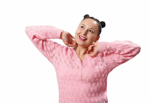 Милая молодая женщина в мечтательной позе. в розовой куртке на белом фоне.