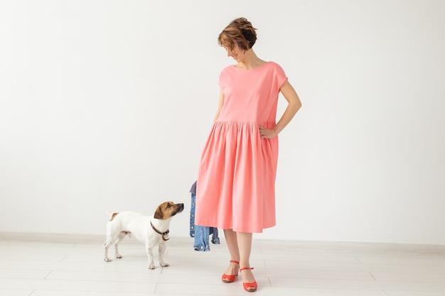 白い壁に彼女の最愛の犬とポーズをとってピンクの長いドレスを着たかわいい若い女性。スタイリッシュなカジュアル服のコンセプト。広告スペース