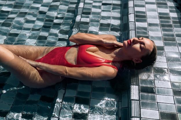 赤い水着のかわいい若い女性がプールで泳ぎます。夏の週末。
