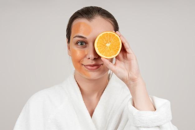 白いローブを着たかわいい若い女性が彼女の顔にオレンジ色のマスクを適用しました