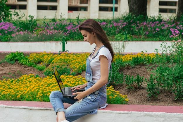 Милая молодая женщина в джинсовом комбинезоне сидит возле клумбы с цветами и смотрит в ноутбук