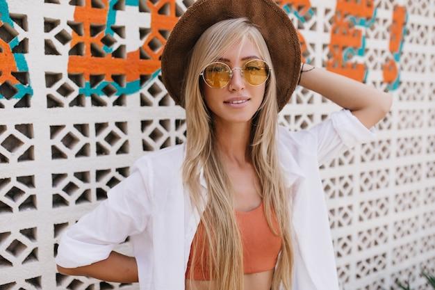 壁の近くでポーズをとってエレガントなシャツと帽子のかわいい若い女性。リゾートでリラックスした黄色のサングラスで愛らしい白人女性の屋外ショット。