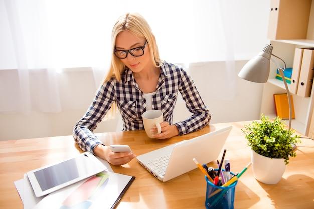 眼鏡をかけたかわいい若い女性は、smsを書いて、オフィスでお茶を飲みます