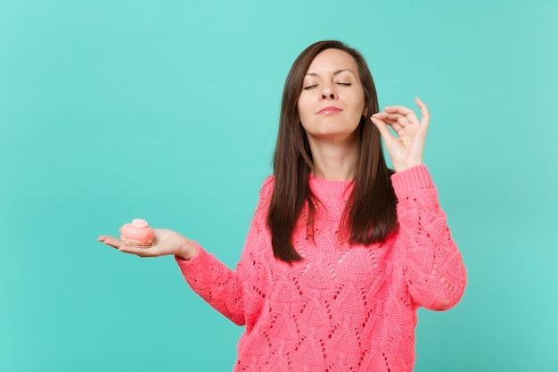 Милая молодая женщина в вязаном розовом свитере с закрытыми глазами держит в руках торт что-то еще, изолированное на синем фоне бирюзовой стены студийный портрет. концепция образа жизни людей. копируйте пространство для копирования.