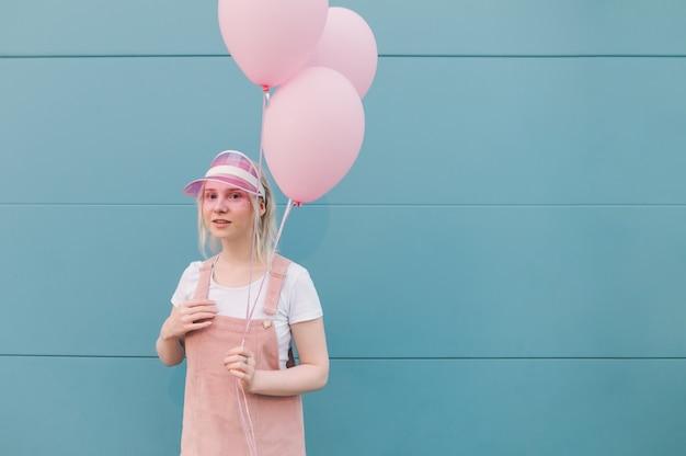 풍선 서 분홍색 옷에 귀여운 젊은 여자