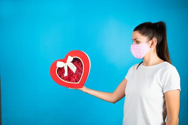 Милая молодая женщина в защитной маске, держащей подарочную коробку валентинок в форме красного сердца на синем.