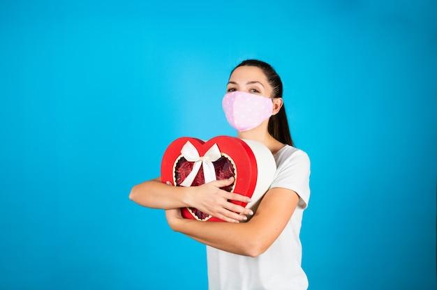 Милая молодая женщина в защитной маске, обнимая подарочную коробку валентинок в форме красного сердца на синем.