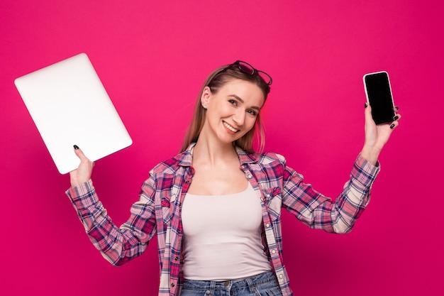 Милая молодая женщина в стильной одежде держит телефон и ноутбук на розовом фоне