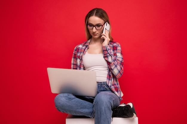 Милая молодая женщина в стильной одежде разговаривает по телефону и работает с ноутбуком на красном фоне