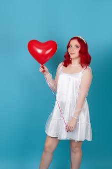 흰 드레스와 비행 하트 모양의 풍선을 들고 빨간 머리에 귀여운 젊은 여자