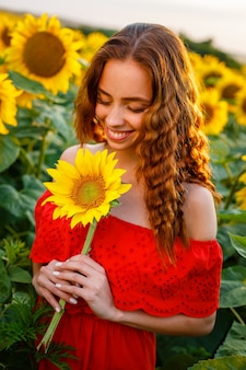 귀여운 젊은 여자는 일몰 아름다운 부드러운 일몰 필드에 서있는 동안 그녀의 손에 해바라기를 잡고있다.