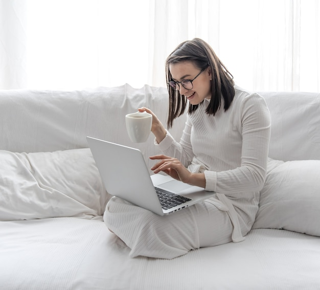 A cute young woman is sitting at home on a white sofa in a white dress in front of a laptop