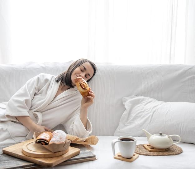 Una giovane donna carina è seduta sul divano in una vestaglia con un panino in mano.
