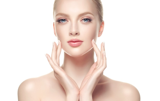 Cute, young woman is touching soft skin of the face by graceful fingers of hands