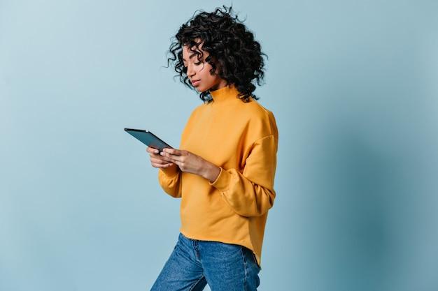 Carina giovane donna in jeans utilizzando la tavoletta digitale