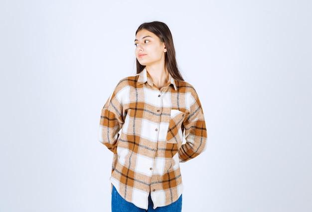 Carino giovane donna guardando il suo fianco sul muro bianco.