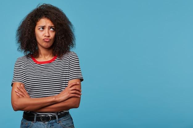 かわいい若い女性は、縞模様のtシャツを着て腕を組んで立っている腹を立てて怒鳴った唇に見えます