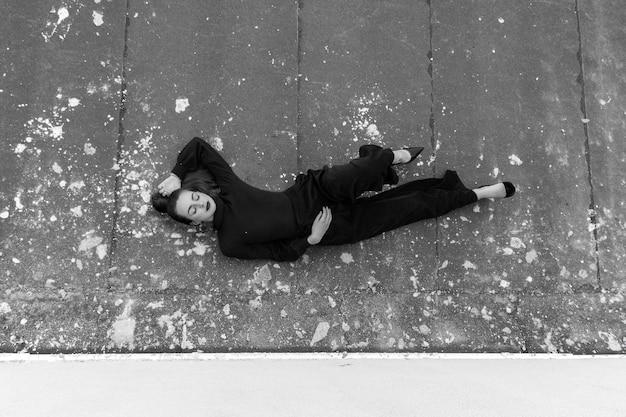 完全な黒い服とポニーテールの髪型で屋根の上に横たわっているかわいい若い女性。黒と白。