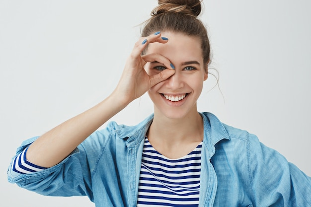 Cute young woman making monocle gesture and looking through fingers