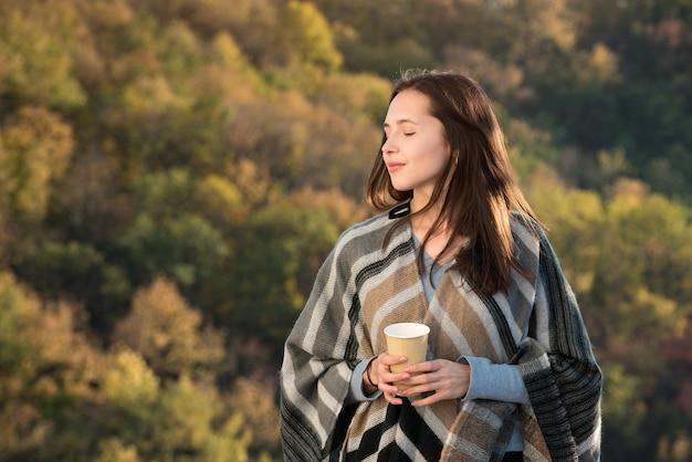 배경가 숲에 귀여운 젊은 여자. 잠겨있는 기분 꿈.