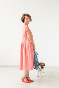 Cute young woman in a pink long dress posing with her beloved dog on a white wall. concept of stylish casual clothes.