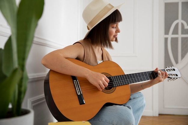 Cute young woman playing guitar indoors