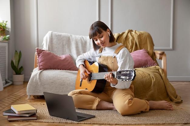 屋内でギターを弾くかわいい若い女性
