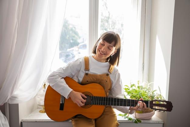 실내에서 기타를 연주하는 귀여운 젊은 여성