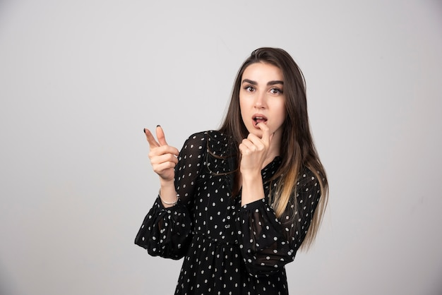 Cute young woman pointing a finger away on a gray wall.