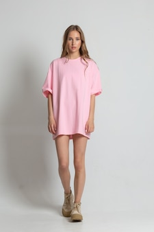 白い背景の上のピンクのtシャツでフルハイトポーズをとってかわいい若い女性