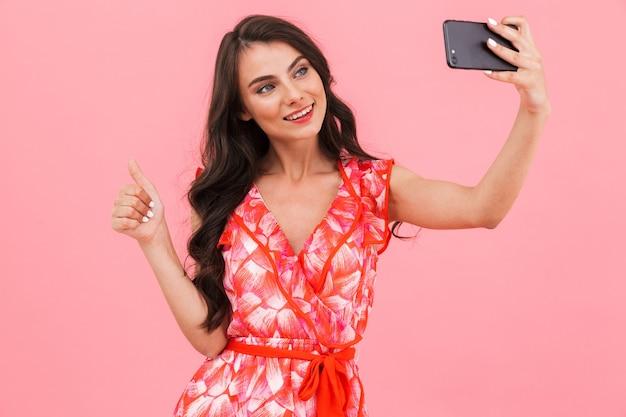 孤立した壁をポーズするかわいい若い女性は、携帯電話で自分撮りを取ります。
