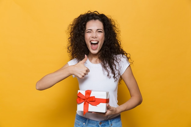 Cute young woman posing isolated on yellow holding gift box present make thumbs up gesture.