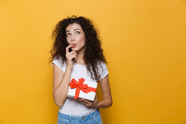 Cute young woman posing isolated on yellow holding gift box present.
