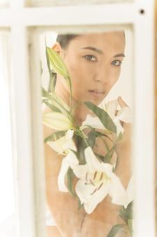 실내에서 꽃다발을 들고 포즈를 취하는 귀여운 젊은 여성