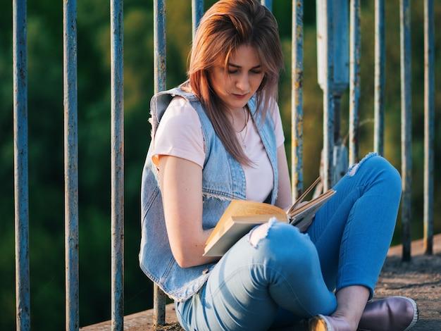 橋の上に座って本を読んでかわいい若い女性