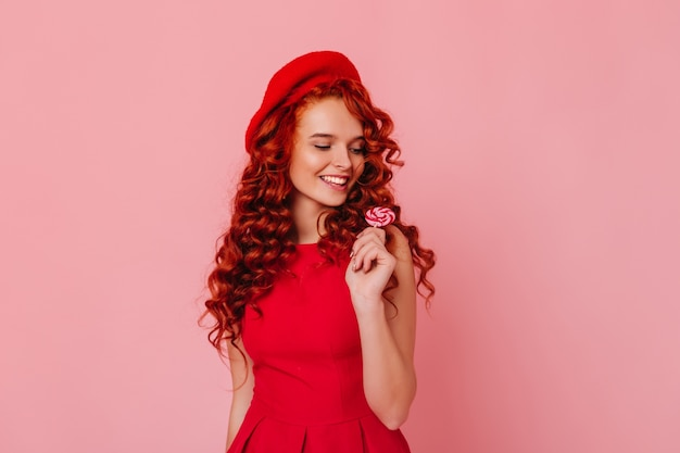 Cute young woman in red dress and felt hat posing with lollipop on pink space.
