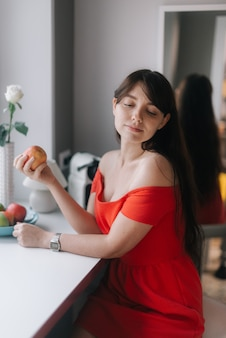 Cute young woman in red dress holding a large apple in her hand